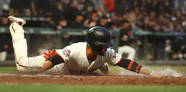 San Francisco Giants' Gregor Blanco slides to score against the Cincinnati Reds in the second inning of a baseball game Monday, May 14, 2018, in San Francisco. Blanco scored on a double by Giants' Andrew McCutchen. (AP Photo/Ben Margot)