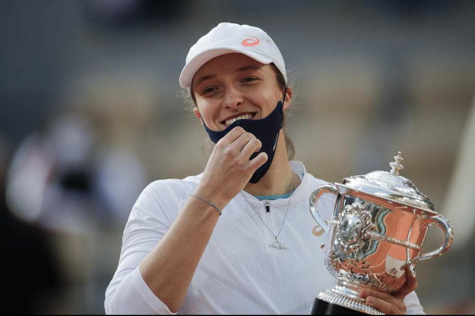 FILE - In this Saturday, Oct. 10, 2020 file photo, Poland's Iga Swiatek holds the trophy after winning the final match of the French Open tennis tournament against Sofia Kenin of the U.S. in two sets 6-4, 6-1, at the Roland Garros stadium in Paris, France. French Open champion Iga Swiatek said she will quarantine after meeting with Poland President Andrzej Duda. Duda's office announced Saturday, Oct. 24, 2020 that he tested positive for coronavirus. The 19-year-old Swiatek met with Duda on Friday. (AP Photo/Christophe Ena, File)