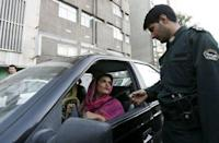 A policeman asks a woman wearing bright coloured clothes for her identification papers at a morals police checkpoint in Tehran in this June 16, 2008 file photo. REUTERS/Stringer/Files