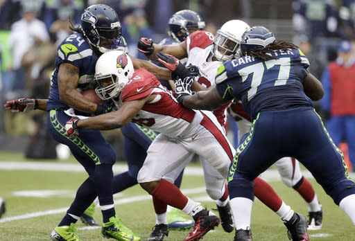Seattle Seahawks running back Marshawn Lynch, left, is tackled by Arizona Cardinals tight end Jake Ballard, center, as Seahawks' James Carpenter (77) stands near, in the first half of an NFL football game, Sunday, Dec. 22, 2013, in Seattle. (AP Photo/Elaine Thompson)