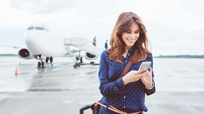 Woman using smartphone in front of aeroplane