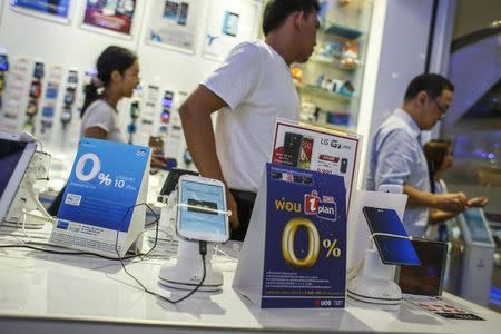 File photo of people walking inside a mobile phone shop at a department store in Bangkok