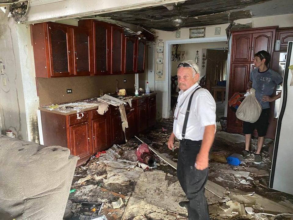 Durle Blanchard and his son Louis examine the damage inside his home in Chauvin, Louisiana nearly one month after Hurricane Ida. (Alex Woodward)