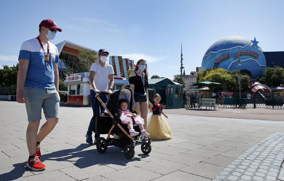 PARIS, FRANCE - JULY 13: People with annual passes wearing protective face masks arrive to visit Disneyland Paris on July 13, 2020 in Marne-la-Vallee, near Paris, France. After four months of closure, the amusement park officially reopens its doors on Wednesday July 15 with compulsory reservations online. The Disneyland Paris and Walt Disney studio parks have been closed since mid-March due to the coronavirus epidemic (COVID 19). (Photo by Chesnot/Getty Images)