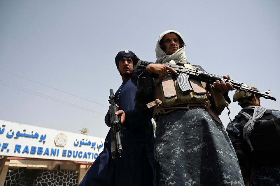 Taliban fighters escort veiled women marching during a pro-Taliban rally outside the Shaheed Rabbani Education University in Kabul on September 11, 2021.