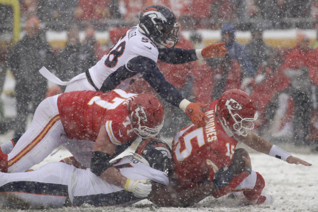 Kansas City Chiefs quarterback Patrick Mahomes (15) is brought down by Denver Broncos defensive end Shelby Harris, bottom, and linebacker Von Miller (58), during the first half of an NFL football game in Kansas City, Mo., Sunday, Dec. 15, 2019. (AP Photo/Charlie Riedel)