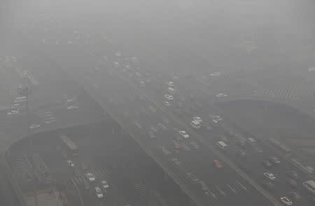 Vehicles drive through the Guomao Bridge on a heavy haze day in Beijing's central business district January 29, 2013. REUTERS/Jason Lee