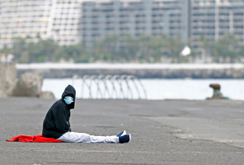 A migrant rescued in the Atlantic Ocean sits on the ground after disembarking from a Spanish coast guard vessel, in the port of Arguineguin