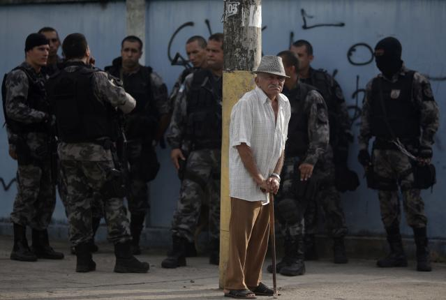 An elderly man stands next to police officers as they patrol at the Vila Kennedy slum during an operation to install the Police Peacekeeping Unit (UPP) in the region in Rio de Janeiro March 13, 2014. The introduction of the peacekeeping program in the region is part of efforts to crack down on crime and increase security as the city prepares to host the 2014 World Cup soccer tournament and the 2016 Olympic Games. REUTERS/Ricardo Moraes (BRAZIL - Tags: CRIME LAW CIVIL UNREST)