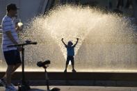 A boy plays in a fountain at VDNKh (The Exhibition of Achievements of National Economy) in Moscow, Russia, Sunday, June 20, 2021. The hot weather in Moscow is continuing, with temperatures forecast to reach over 30 degrees Celsius (86 Fahrenheit). (AP Photo/Alexander Zemlianichenko)