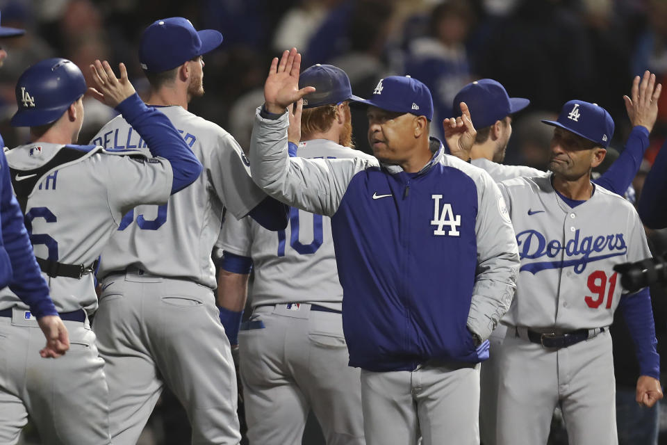 Los Angeles Dodgers manager Dave Roberts, middle right, celebrates with his team after the Dodgers defeated the San Francisco Giants in Game 2 of a baseball National League Division Series Saturday, Oct. 9, 2021, in San Francisco. (AP Photo/Jed Jacobsohn)