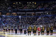 Vancouver Canucks and Colorado Avalanche players stand on the ice before the singing of the national anthems as spectators hold up cell phones with the flashlights turned on in support of those battling cancer, at an NHL hockey game Saturday, Nov. 16, 2019, in Vancouver, British Columbia. (Darryl Dyck/The Canadian Press via AP)