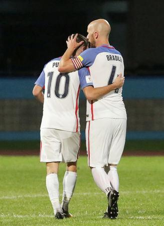 Christian Pulisic and Michael Bradley hug. REUTERS/Andrea de Silva