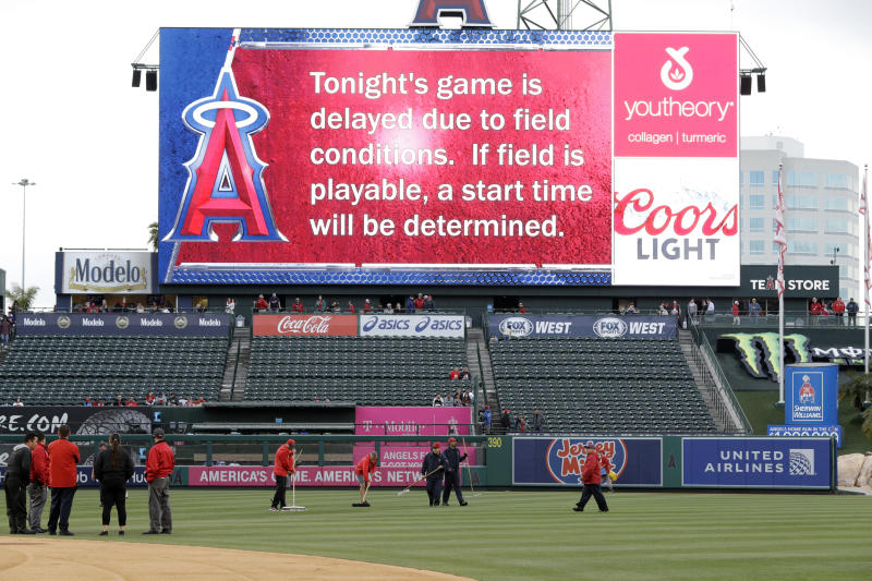 Members of the grounds crew try to clear water from the outfield before a baseball game between the Los Angeles Angels and the Minnesota Twins on Wednesday, May 22, 2019, in Anaheim, Calif. The game was postponed. (AP Photo/Marcio Jose Sanchez)