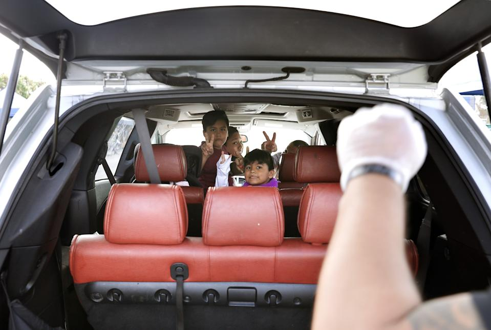 Parents and their two children look out the back of their minivan and gesture toward a volunteer with their fist in the air