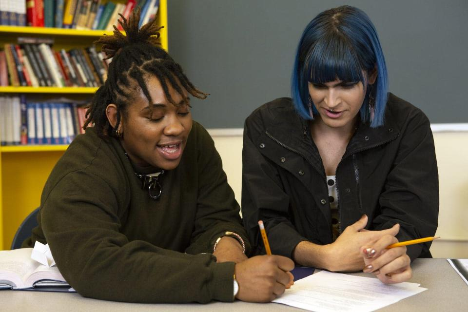 One young person is helping another with their school work in a library setting.