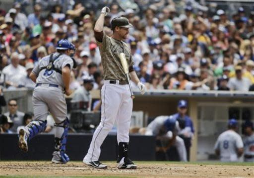 San Diego Padres' Chase Headley flips away his bat as Los Angeles Dodgers catcher Tim Federowicz heads for the dugout after Headley struck out to end the fourth inning of a baseball game in San Diego, Sunday, June 23, 2013. (AP Photo/Lenny Ignelzi)