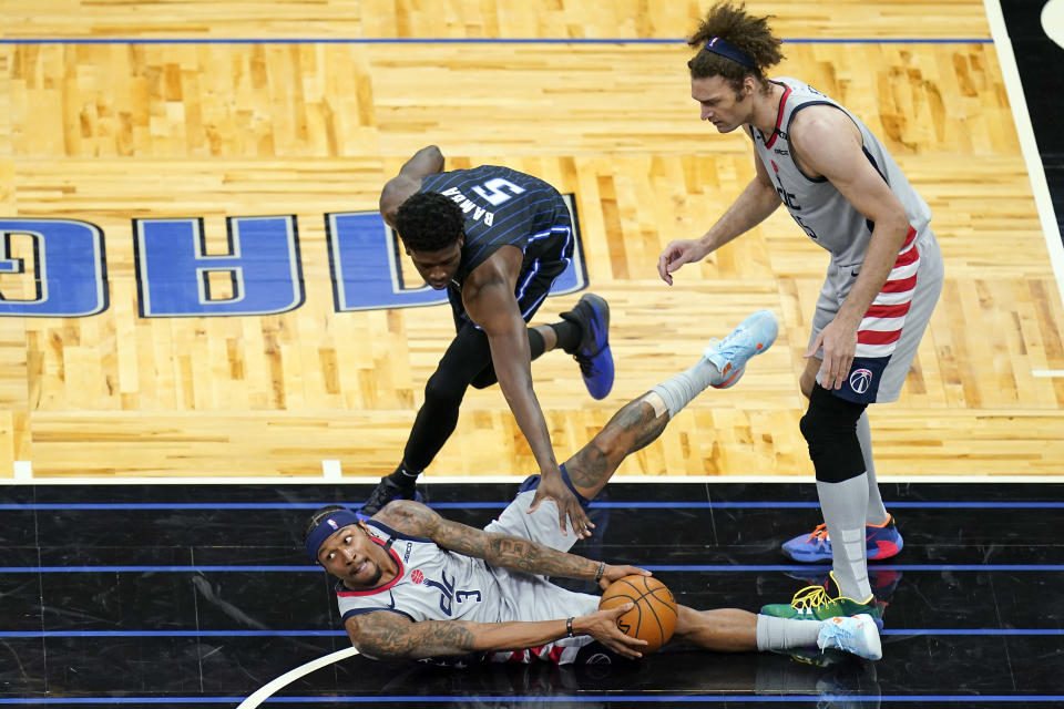 Washington Wizards guard Bradley Beal (3) looks to pass the ball as Orlando Magic center Mo Bamba (5) defends and Wizards center Robin Lopez, right, watches during the second half of an NBA basketball game, Wednesday, April 7, 2021, in Orlando, Fla. (AP Photo/John Raoux)
