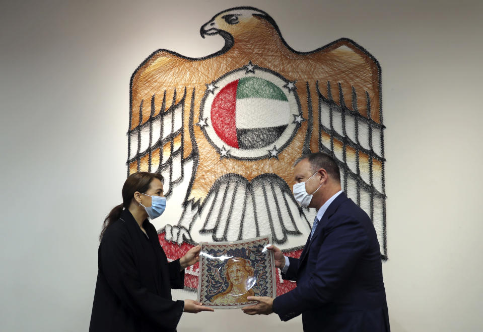 UAE Minister of State for Food and Water Security Mariam al-Muhairi, left, receives a gift from Erel Margalit, founder and chairman of Jerusalem Venture Partners, JVP, at the headquarter of the Government Accelerators in Dubai, United Arab Emirates, Tuesday, Oct. 27, 2020. Another plane full of Israeli business people excited about their newfound access to the UAE has touched down in Dubai this week. It's the latest whirlwind trip seeking to cash in on a U.S.-brokered deal to normalize relations between the countries. (AP Photo/Kamran Jebreili)