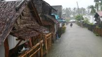 In this photo provided by the San Policarpo Firestation, a man wades through floodwater caused by Typhoon Surigae in the municipality of San Policarpo, Eastern Samar, eastern Philippines on Sunday April 18, 2021. An approaching typhoon has left at least one person dead, another missing and prompted the evacuation of more than 100,000 people as a precaution in the eastern and central Philippines, although the unusual summer storm is not expected to blow into land, officials said Monday. (FO1 Marianne Jabinal/ San Policarpo Firestation via AP)