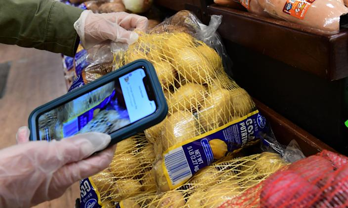 Instacart employee Monica Ortega uses her cellphone to scan items for an order