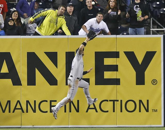 Colorado Rockies left fielder Carlos Gonzalez goes up to snare a deep drive hit by San Diego Padres' Nick Hundley with a runner on base in the seventh inning of a baseball game Tuesday, April 15, 2014, in San Diego. (AP Photo/Lenny Ignelzi)