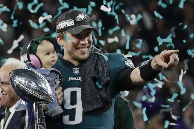 Philadelphia's Nick Foles holds his daughter, Lily, after beating New England in Super Bowl LII,  (AP)