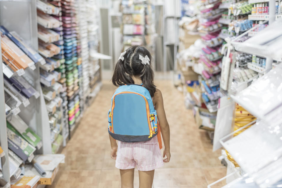 little girl in store with backpack ready for by school material