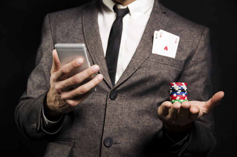 A man in a grey suit viewed from the neck down holds a smartphone in one hand and poker chips in the other and two aces in his jacket pocket.