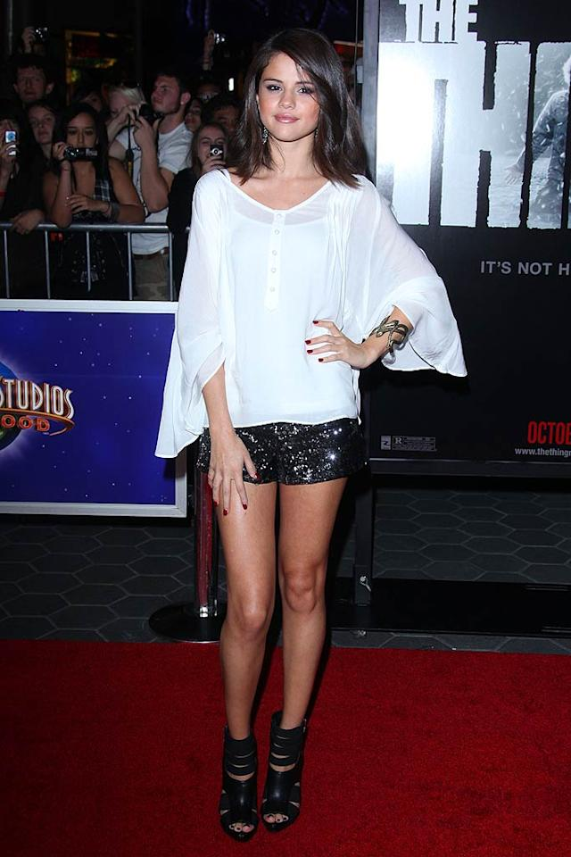 "Back in L.A., Justin Bieber's better half -- Selena Gomez -- hit the red carpet for the premiere of ""The Thing,"" where she perfectly paired a billowing white top with a serpentine cuff, sequined shorts, and strappy heels.  Jen Lowery/Splash News - October 10, 2011"