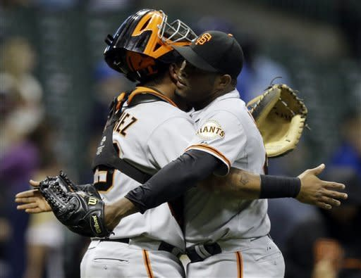 San Francisco Giants catcher Hector Sanchez hugs relief pitcher Santiago Casilla after the 14th inning of a baseball game against the Milwaukee Brewers, Monday, May 21, 2012, in Milwaukee. The Giants won 4-3. (AP Photo/Morry Gash)