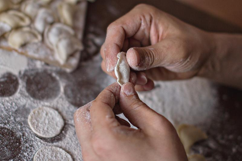 in male palms dough in the process of molding dumplings on the background of the table with flour and round dough blanks