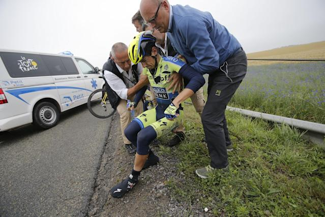 Tinkoff Saxo team manager Bjarne Riis of Denmark, right, helps his rider Jesus Hernandez Blaquez of Spain after he crashed during the sixth stage of the Tour de France cycling race over 194 kilometers (120.5 miles) with start in Arras and finish in Reims, France, Thursday, July 10, 2014. Blaquez is a key climbing lieutenant for leader Alberto Contador of Spain, but had to abandon the race because of his injuries. (AP Photo/Christophe Ena)