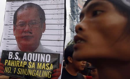 A placard containing an image of Philippines' President Benigno Aquino is seen near a protester after demonstrators were blocked from marching towards Batasang Pambansa, where Aquino will address the joint session of Congress delivering his last State of the Nation address in Quezon city, Metro Manila, in the Philippines July 27, 2015. REUTERS/Erik De Castro