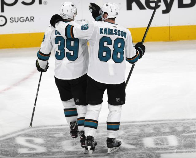 San Jose Sharks center Melker Karlsson, right, congratulates center Logan Couture after his empty-net goal against the Colorado Avalanche during the third period of Game 3 of an NHL hockey second-round playoff series Tuesday, April 30, 2019, in Denver. The Sharks won 4-2. (AP Photo/David Zalubowski)