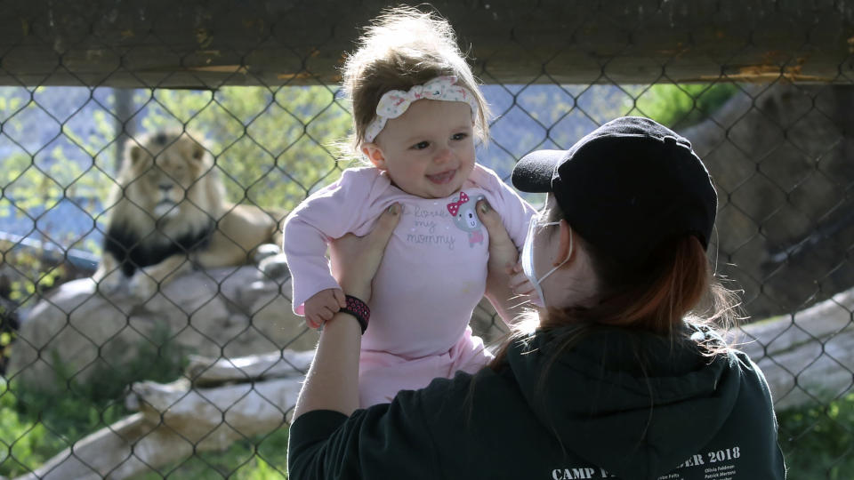 Holly Stuart holds her daughter Savannah during a visit to Utah's Hogle Zoo Saturday, May 2, 2020, in Salt Lake City. The zoo is one of many Utah businesses reopening Saturday amid the Coronavirus pandemic after multi-week closure. The zoo will restrict the number of guests who enter per day to help with social distancing. (AP Photo/Rick Bowmer)