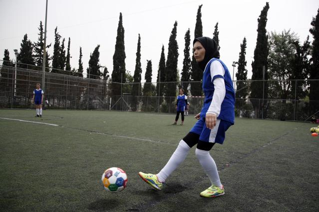 In this Wednesday, April 24, 2019 photo, Fatima from Afghanistan passes the ball during a training session of Hestia FC Women's Refugee Soccer team in Athens. Many of the players at Hestia FC weren't allowed to play or even watch soccer matches in their home countries. Hestia FC was set up by the Olympic Truce Centre, a non-government organization created in 2000 by the International Olympic Committee and Greek Foreign Ministry. (AP Photo/Thanassis Stavrakis)