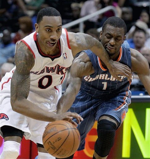 Charlotte Bobcats' Kemba Walker, right, reaches for the ball against Atlanta Hawks' Jeff Teague in the second quarter of an NBA basketball game onWednesday, April 4, 2012, in Atlanta. (AP Photo/David Goldman)