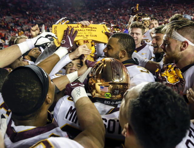 FILE - In this Nov. 24, 2018, file photo, Minnesota players celebrate with the Paul Bunyan Axe trophy after beating Wisconsin 37-15 in an NCAA college football game, in Madison, Wis. There's far more at stake in the final game of the season for Minnesota than just a traveling trophy, for once, as the ninth-ranked Gophers host 13th-ranked Wisconsin for Paul Bunyan's Axe and a first-ever spot in the Big Ten championship game. The Badgers have been there five times before. (AP Photo/Andy Manis, File)