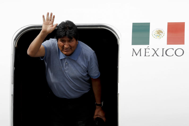 Former Bolivian President Evo Morales waves upon arrival to Mexico City, Tuesday, Nov. 12, 2019. Mexico granted asylum to Morales, who resigned on Nov. 10 under mounting pressure from the military and the public after his re-election victory triggered weeks of fraud allegations and deadly protests. (AP Photo/Eduardo Verdugo)
