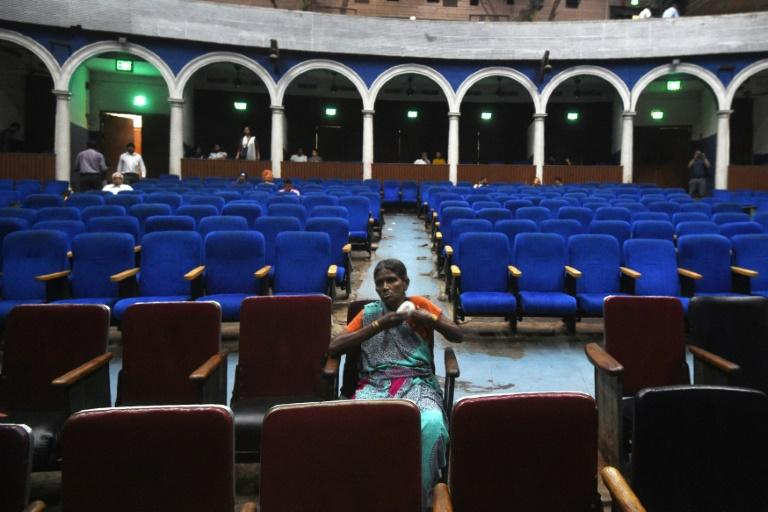A spectator waits for a film showing at the Regal cinema in the heart of the Indian capital New Delhi