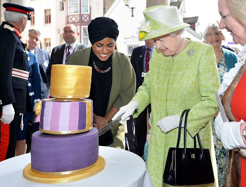 Britain's Queen Elizabeth II cuts into a birthday cake baked by Nadiya Hussain, left, winner of the Great British Bake Off, during celebrations of her 90th birthday in Windsor, England, Thursday April 21, 2016. (John Stillwell/Pool via AP)