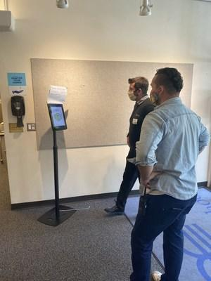 """RealNetworks' Mike deVoss (in dark sweater) installs MaskCheck kiosk in """"active mode"""" at the South (staff) entrance of The Bush School in Seattle, and shows Facilities Director Michael Miller how it works."""