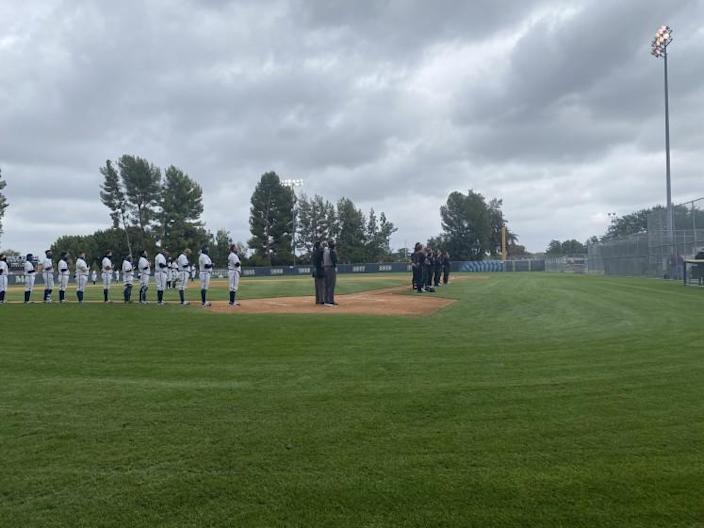 Birmingham and JSerra players standing for the national anthem on a cloudy Tuesday in Lake Balboa.