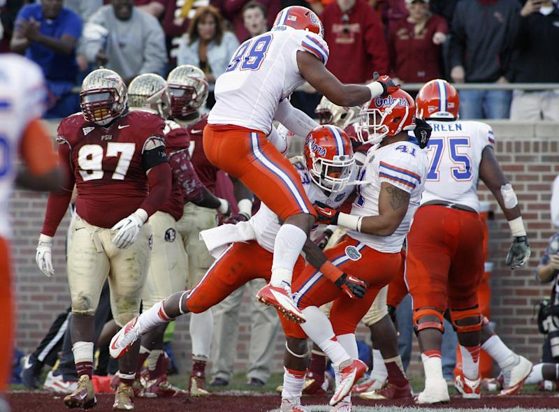 Florida running back Mike Gillislee, (23) center, is mobbed by teammates including running back Hunter Joyer (41) after a 9-yard touchdown run during the first half of an NCAA college football game, Saturday, Nov. 24, 2012, in Tallahassee, Fla. (AP Photo/Phil Sears)
