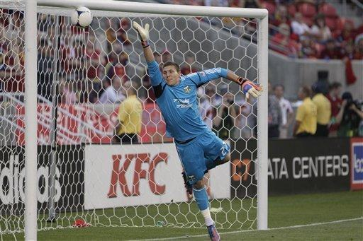 Portland Timbers' goalie Joe Bendik (23) reaches for the ball before it goes into the goal in the first half of an MLS soccer game with Real Salt Lake Saturday, Sept. 22, 2012, in Sandy, Utah. Real Salt Lake midfielder Javier Morales scored the goal. (AP Photo/Rick Bowmer)