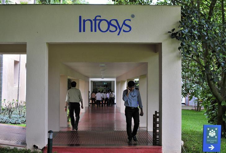 Employees walk along a corridor in the Infosys campus in Bangalore