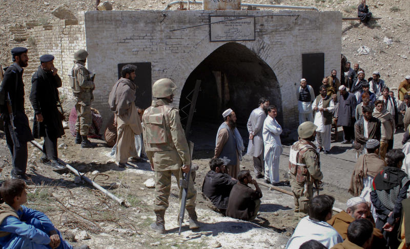 Pakistan army soldier, mine workers and local residents gather outside a coal mine after a explosion in Sorange near Quetta, Pakistan on Sunday, March 20, 2011. A methane gas explosion in a coal mine in southwestern Pakistan killed at least six miners and trapped 46 others, a top mining official said. (AP Photo/Arshad Butt)