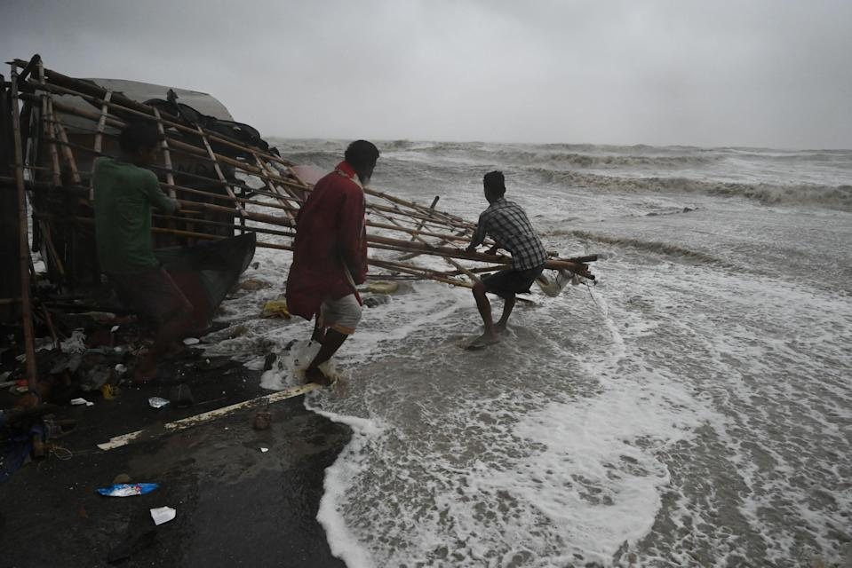 <p>Residents shift makeshift stalls as water reaches a road at a beachfront area in the state of Odisha's Balasore district</p> (Dibyangshu Sarkar/AFP via Getty Images)