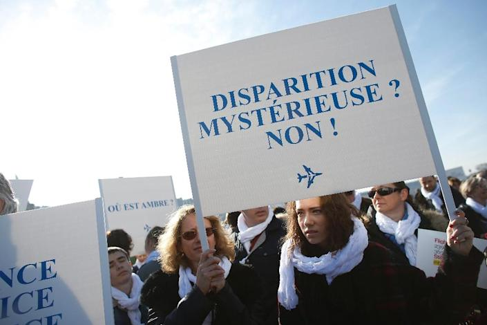 """A woman holds up a banner that reads """"Mysterious disappearance ? No!"""" during a silent march towards the Elysee Palace in Paris on the first anniversary of the disappearance of flight MH370, on March 8, 2015 (AFP Photo/Thomas Samson)"""